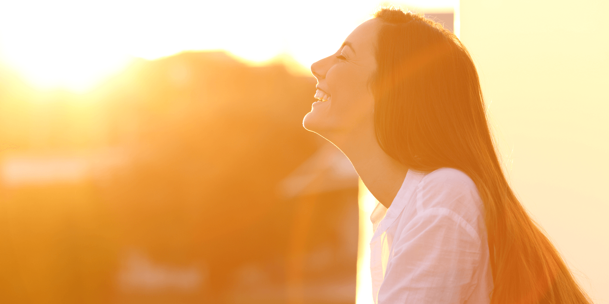 Woman looking skyward enjoying sun on face.