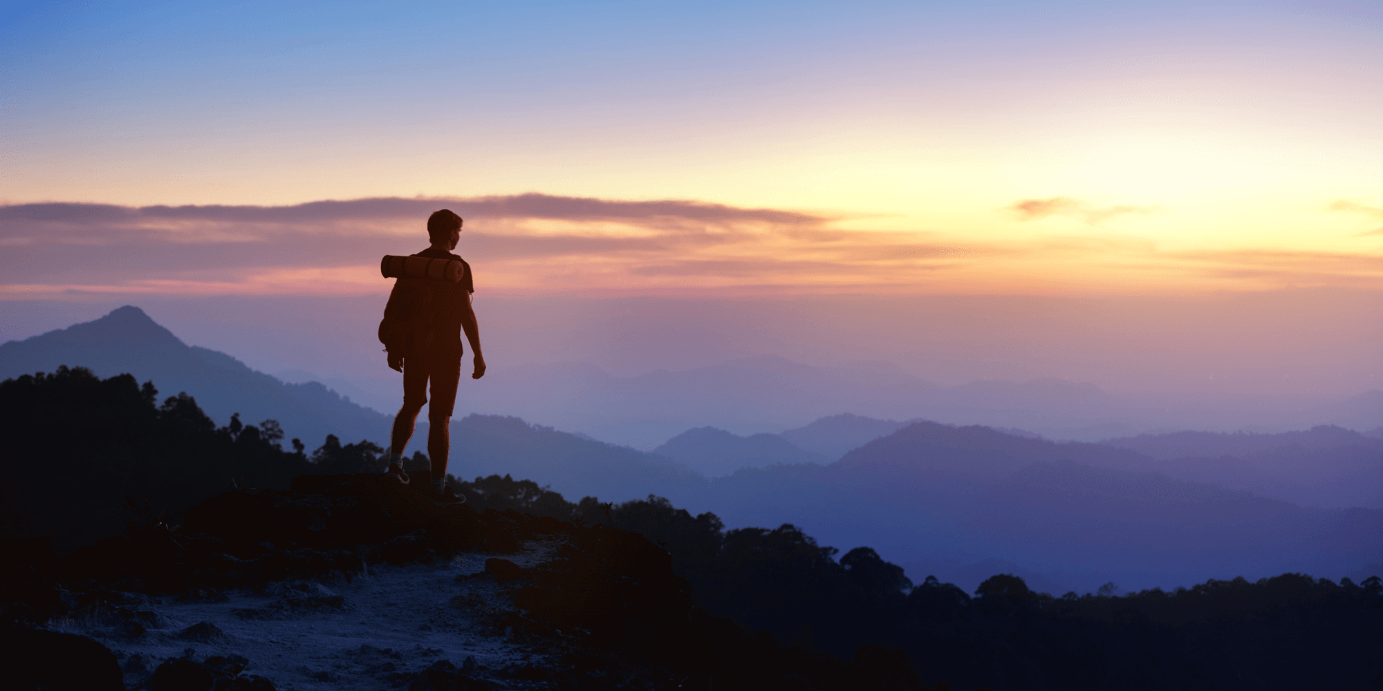 silhouette of man hiking and looking at purple sunset